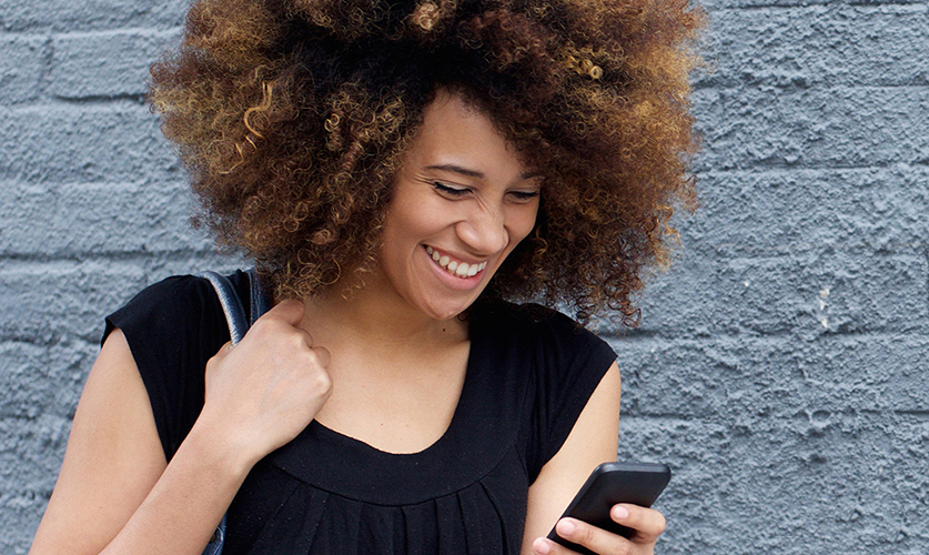 Beautiful Afro American girl in casual clothes is using a smart phone and smiling while standing