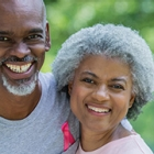 Senior African American couple smile before running in charity breast cancer awareness marathon