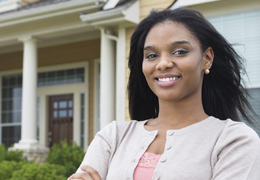 African American woman standing outside her house smiling at the camera